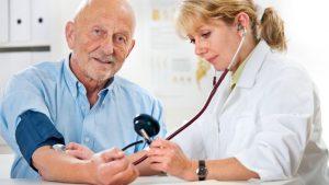 Female doctor measuring blood pressure of senior man